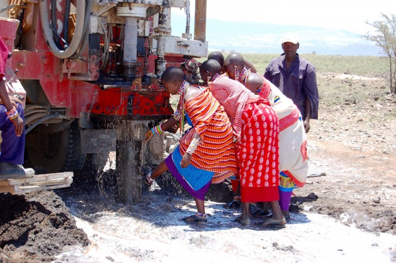 Women touch the water as it pours out of the well
