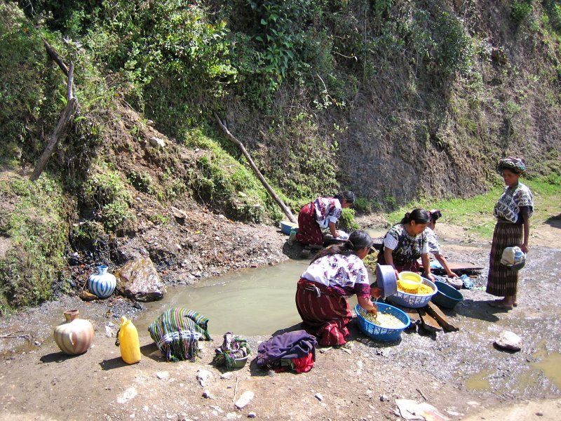 Women washing food and clothes in mud puddle next to road, Guatemala
