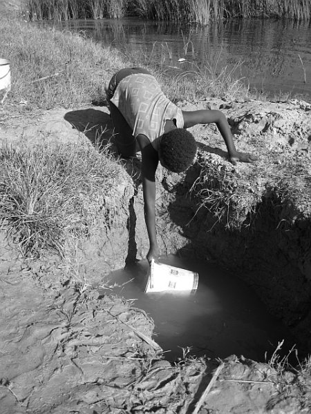 Boy finding water in a ditch, Botswana