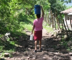 Woman walking with water, Nicaragua