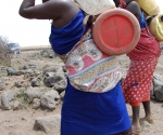 Women carrying water on backs, Kenya